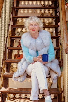 Senior stylish woman in fur coat and with grey hair sitting on carousel drinking tea coffee
