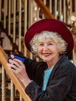 濃い灰色のコートの帽子とカルーセル飲酒cofのそばに立っている灰色の髪のシニアスタイリッシュな女性