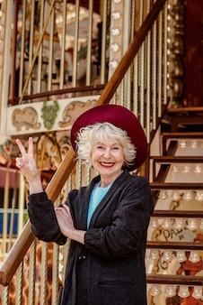 ダークグレーのコートの帽子とカルーセルの笑顔で立っている灰色の髪のシニアスタイリッシュな女性