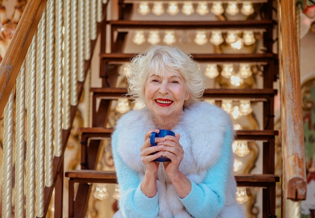 毛皮のコートを着て、ティーコーヒーを飲むカルーセルに座っている白髪のシニアスタイリッシュな女性