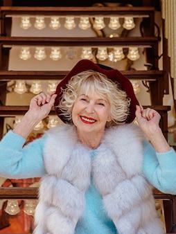 毛皮のコートを着て、紫色の帽子を保持しているカルーセルに座っている白髪のシニアスタイリッシュな女性旅行