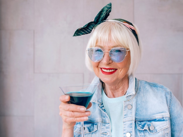 Senior stylish woman with gray hair and in blue glasses and jeans jacket holding cocktail