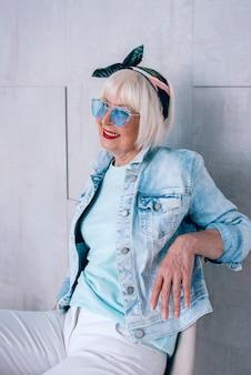 세련된 머리띠와 파란색 안경과 데님 재킷을 입은 회색 머리를 한 세련된 고위 여성