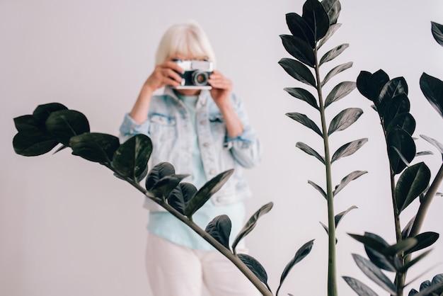 Старшая стильная женщина с седыми волосами в очках и джинсовой куртке фотографирует цветы пленочной камерой