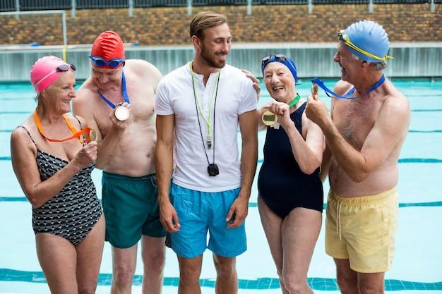 수영장에서 트레이너에게 메달을 보여주는 수석 수영