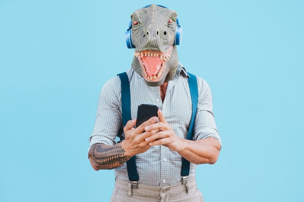 Senior tattooed man with t-rex mask using smartphone while listening music