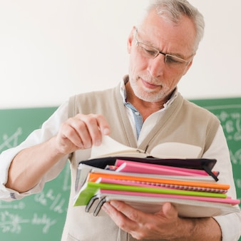 Senior teacher checking notepads in classroom