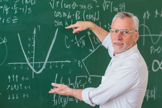 Senior teacher in glasses explaining math example on green chalkboard