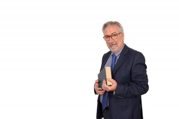 Senior teacher standing holding a book