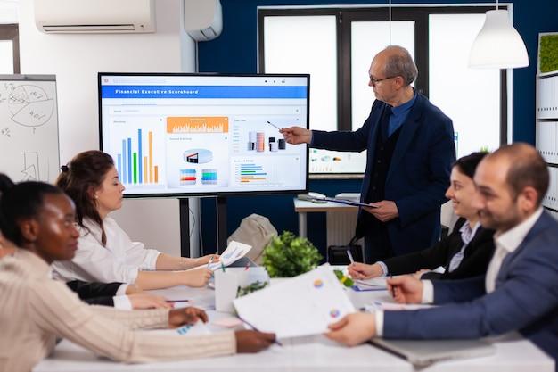 会議室のブリーフィング計画でプレゼンテーションのディスカッションを説明するシニアチームリーダー。画面を見ている同僚と新しいビジネスアプリケーションについて話し合う企業スタッフ
