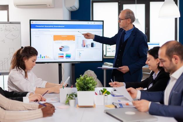 会議室のブリーフィング計画でプレゼンテーションディスカッションを説明するシニアチームリーダー