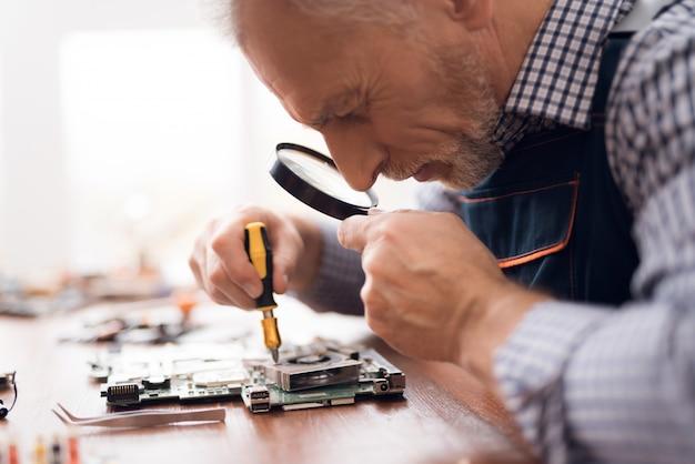 Senior technician master works on circuit board.