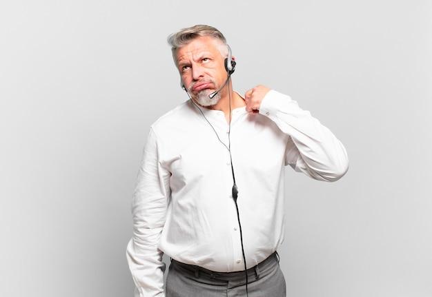 Старший телемаркетер чувствует стресс, тревогу, усталость и разочарование, дергает рубашку за шею, выглядит разочарованным из-за проблемы