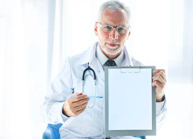 Senior therapist showing blank clipboard