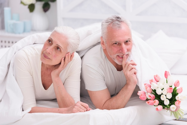 Senior thoughtful woman lying on bed beside her husband doing silence gesture holding tulip flower bouquet