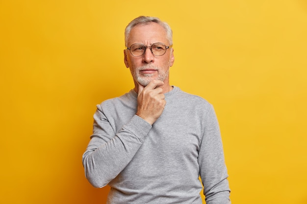 Senior thougthful man holds chin and looks pensively aside makes plannings wears spectacles and casual grey jumper isolated over vivid yellow wall