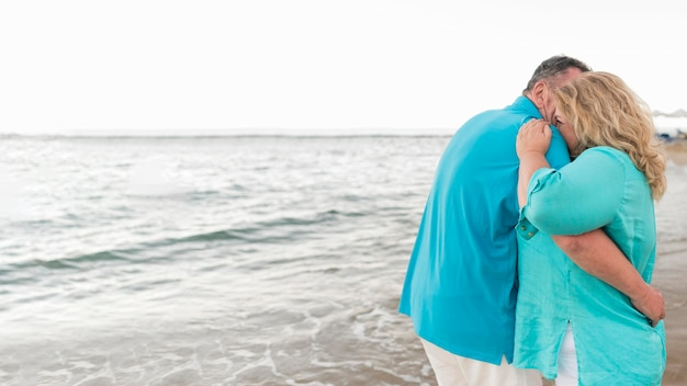 Senior tourist couple embraced on the beach