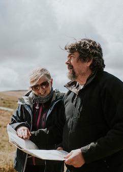 ウェールズ、英国で迷子になっている間に地図を見ているシニア観光カップル