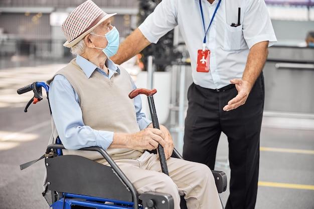 공항 직원에게주의 깊게 듣고 그의 손에 지팡이를 들고 수석 관광