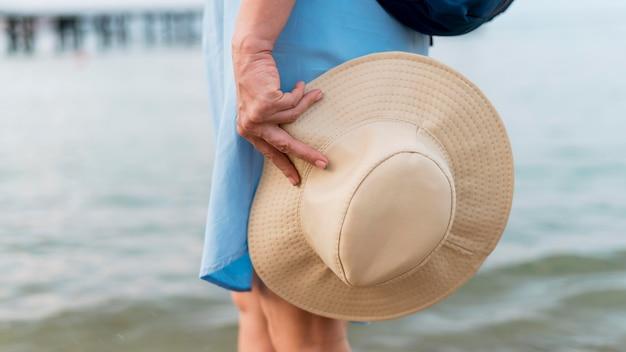 Старшая туристская женщина держа шляпу пляжа