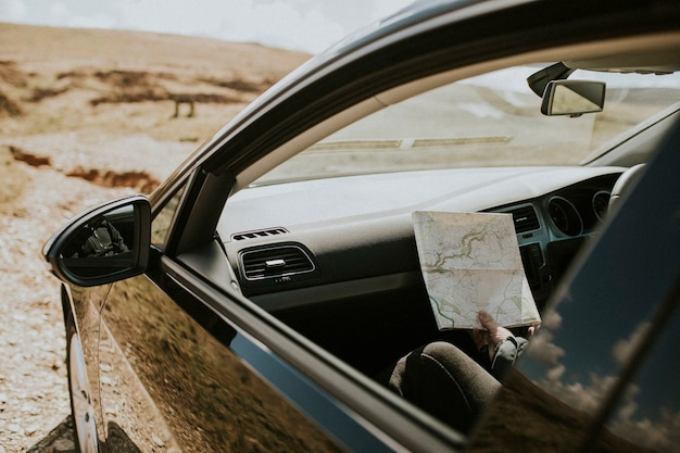 車の中で地図を見ている年配の観光客の女性