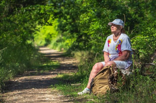 Старшая туристическая женщина на фоне леса. здоровый образ жизни.