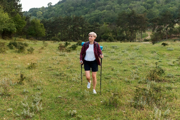 Senior tourist woman outdoors with backpack Free Photo