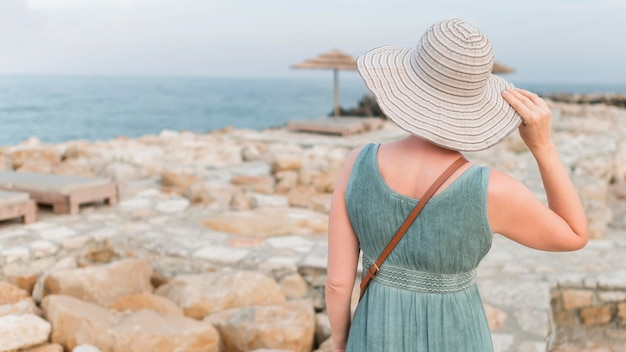 Старшая туристская женщина с шляпой пляжа