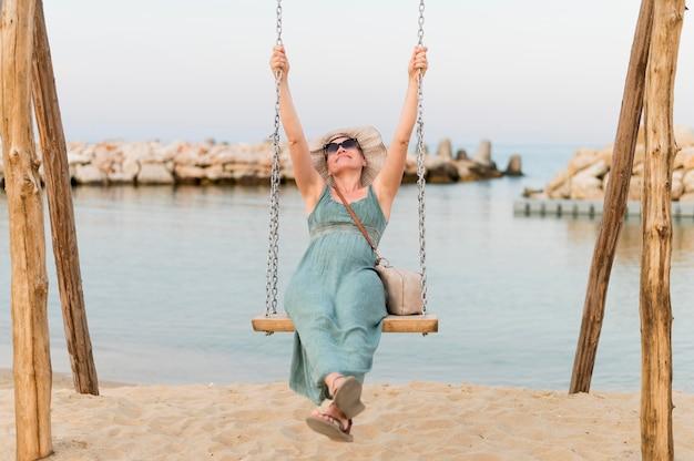 ビーチスイングでサングラスをかけたシニア観光女性