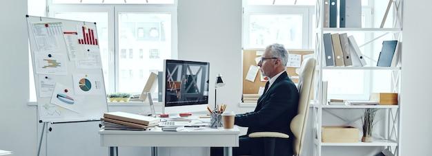 オフィスで働いている間コンピュータを使用してエレガントなビジネススーツのシニアトレーダー