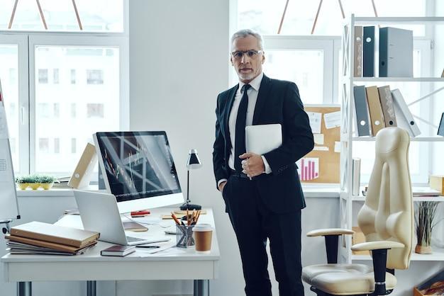 사무실에서 일하는 동안 디지털 태블릿을 사용하는 우아한 비즈니스 정장의 수석 상인