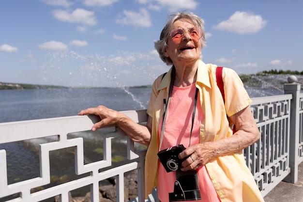 Viaggiatore anziano con in mano una macchina fotografica