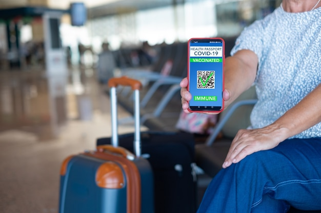 フライトの出発を待っている携帯電話でグリーンパス予防接種パスポートを示している空港のシニア旅行者。コロナウイルスと自由の概念