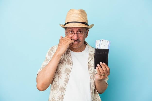 Senior traveler indian middle aged man holding passport isolated on blue background biting fingernails, nervous and very anxious.