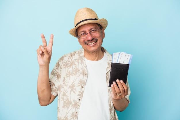 指で平和のシンボルを示す青い背景に分離されたパスポートを持って楽しくてのんきなシニア旅行者インドの中年男性。