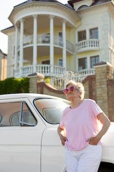 Senior traveler standing nest to her car