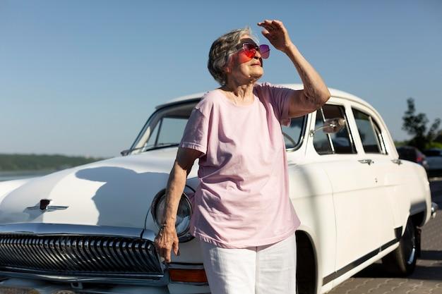 그녀의 차에 둥지를 서 있는 수석 여행자 프리미엄 사진