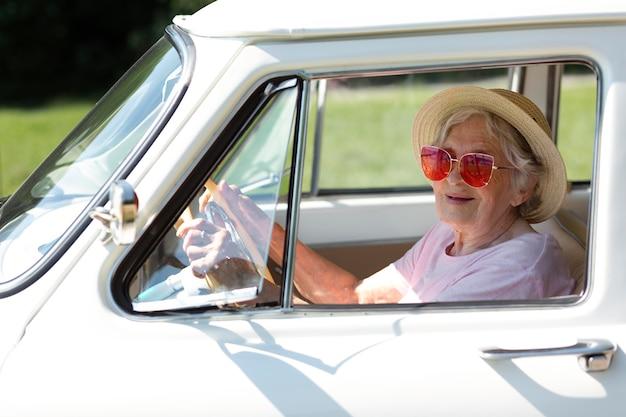 Viaggiatore anziano che indossa occhiali da sole rossi accanto alla sua auto