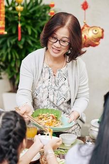 Senior vietnamese woman serving delicious seafood salad at lunar new year celebration