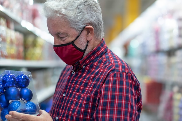 A senior white haired man wearing a medical mask due to coronavirus infection choosing some christmas balls in a store. new normal concept