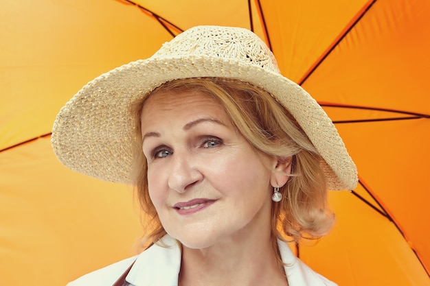 Senior white woman 62 years old with blond hair and hat on her head is standing under orange umbrella.