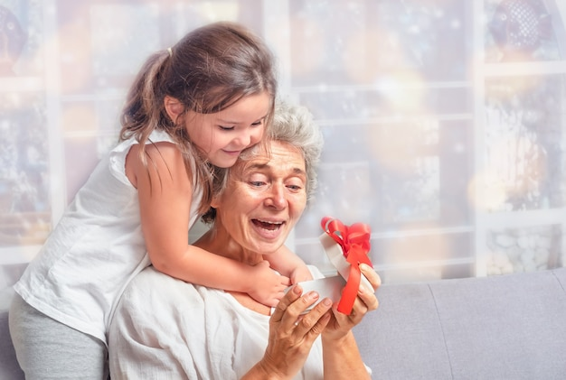 A senior with the child looks into the gift box on the sofa
