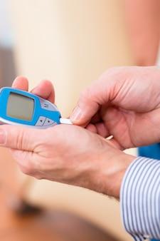 Senior with diabetes using blood glucose analyser