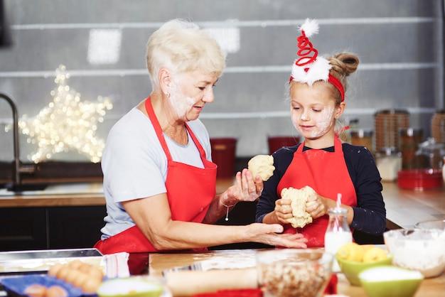 Senior with girl kneading dough in kitchen