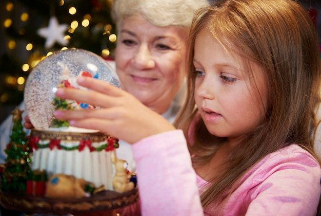 Anziano con la ragazza che guarda il globo della neve di natale