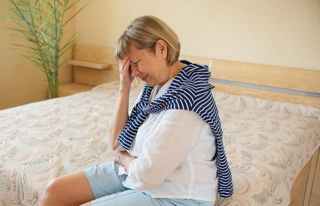 Старшая женщина-наркоман и алкоголизм в одиночку, депрессия, стресс, сидя на кровати, обхватив голову руками. головная боль, головокружение, мигрень. социальные документальные концепции
