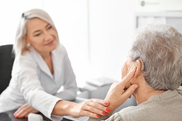 Старшая женщина, регулирующая слуховой аппарат в кабинете врача