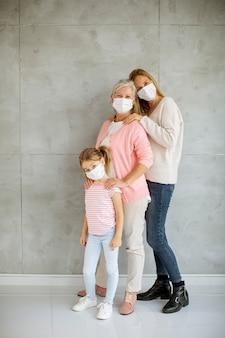 Старшая женщина, взрослая женщина и милая маленькая девочка, три поколения с защитными масками для лица дома