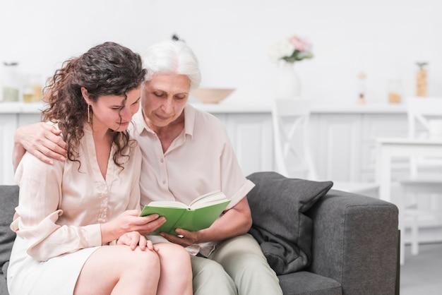 Старший женщина и дочь, читая книги вместе дома