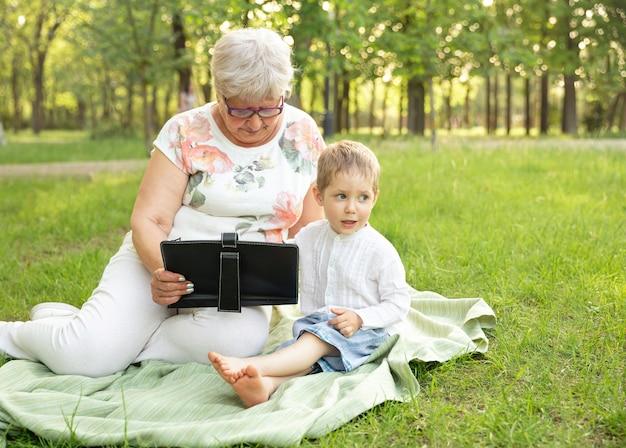 노인 여성과 손자 스마트 장치를 사용하여 공원에서 온라인 쇼핑